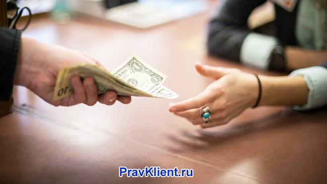 Мужчина передает деньги женщине за столом
