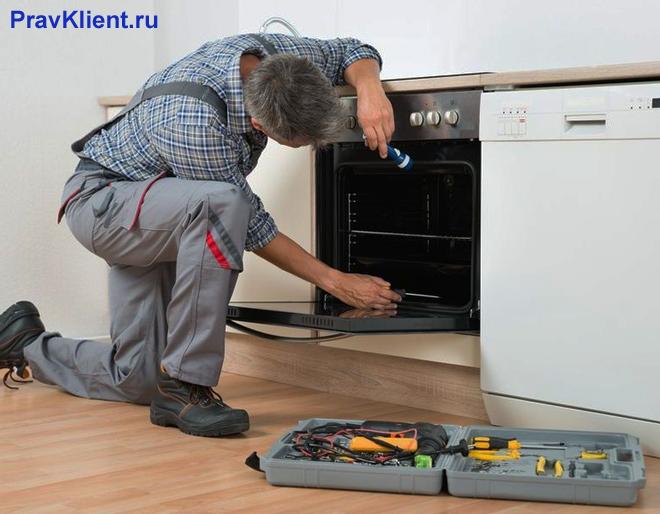 Мужчина ремонтирует духовку