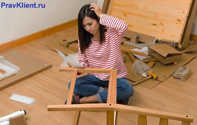 Девушка собирает мебель по инструкции