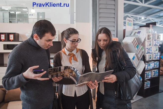 Продавец показывает покупателям каталог мебели