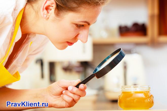 Девушка рассматривает баночку с медом под лупой