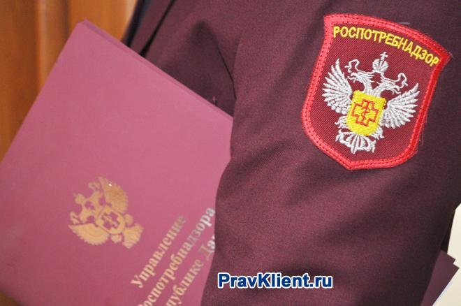 Сотрудник Роспотребнадзора держит в руке папку с документами