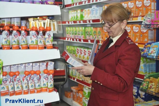 Сотрудница Роспотребнадзора проверяет стеллаж с детским питанием в магазине