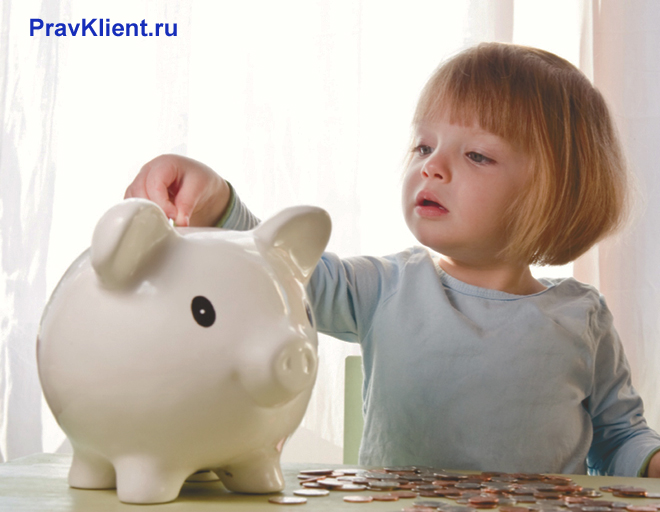 Девочка кидает монетки в копилку-хрюшку