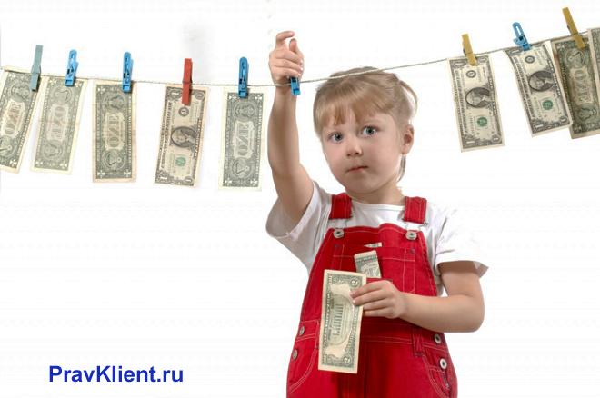 Девочка развешивает на бельевой веревке деньги