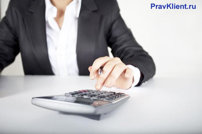 Бизнес-леди считает на калькуляторе