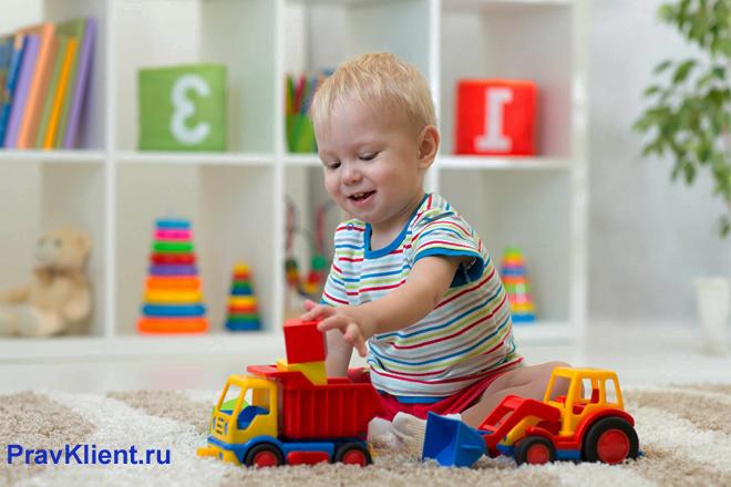 Ребенок играет с детскими машинками в группе детского сада