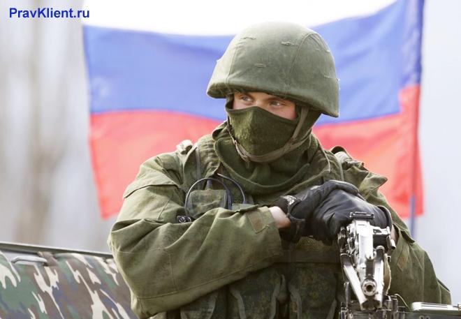 Военный в экипировке на фоне флага РФ