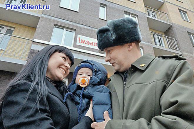 Военнослужащий стоит с семьей на фоне дома