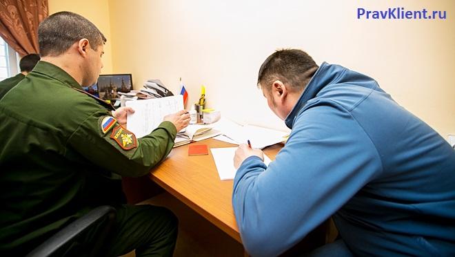 Мужчина и военнослужащий оформляют документы за столом