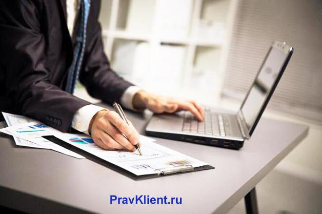 Бизнесмен пользуется ноутбуком и делает записи в тетради