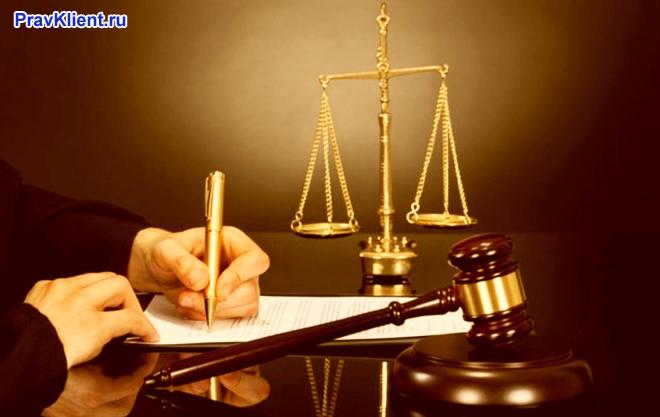 Мужчина пишет на листке бумаги, рядом лежат атрибуты судьи