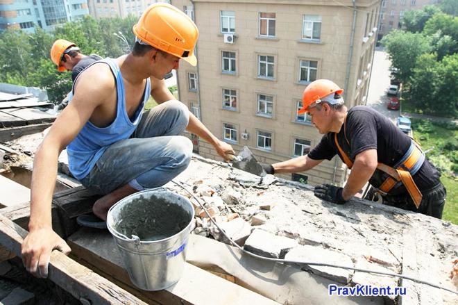 Работники утепляют крышу дома