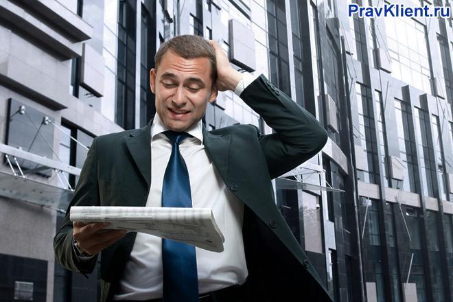 Бизнесмен идет по улице и читает газету