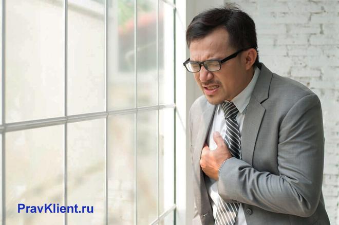Бизнесмен стоит около окна и держится за сердце