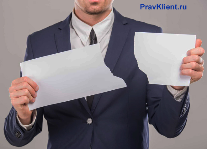 Бизнесмен отрывает от листка бумаги часть