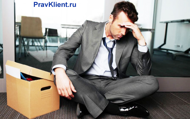 Расстроенный уволенный сотрудник сидит на полу