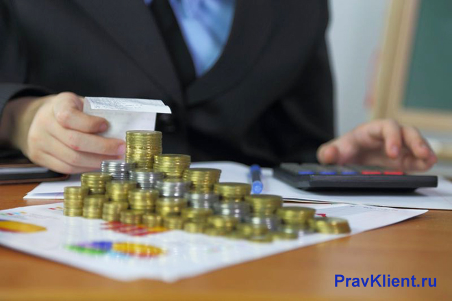 Бизнесмен считает монеты на калькуляторе