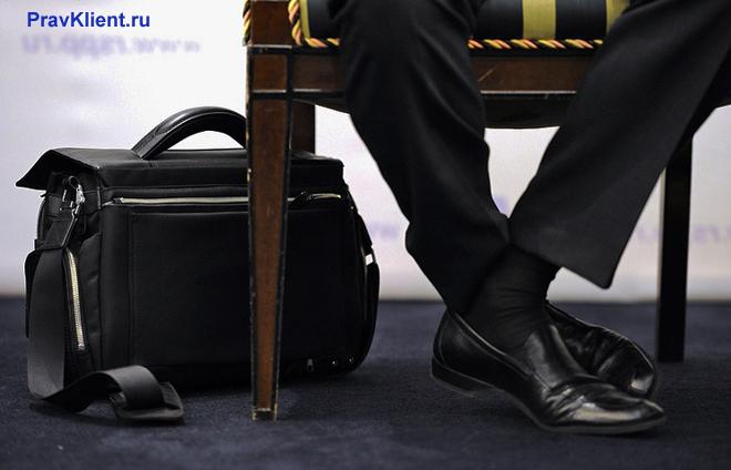 Мужчина в деловом костюме сидит на стуле, на полу стоит портфель