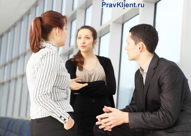 Три коллеги общаются в коридоре