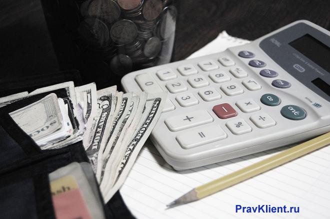 Белый калькулятор, кошелек с деньгами, монеты в банке