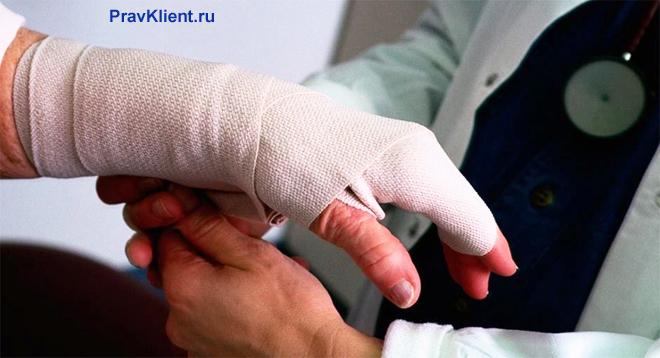 Врач перебинтовывает руку пациенту