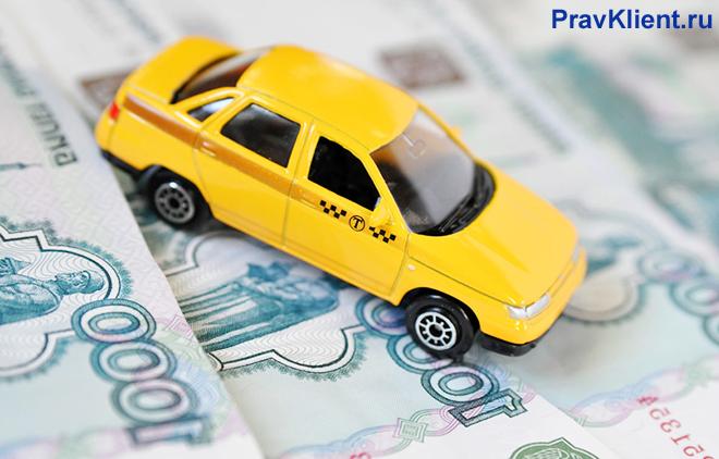 Машина такси стоит на денежных купюрах