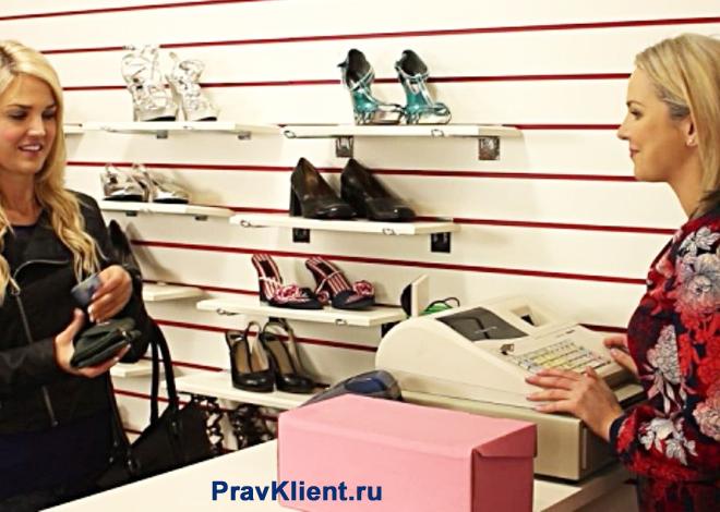 Женщина расплачивается за покупку обуви