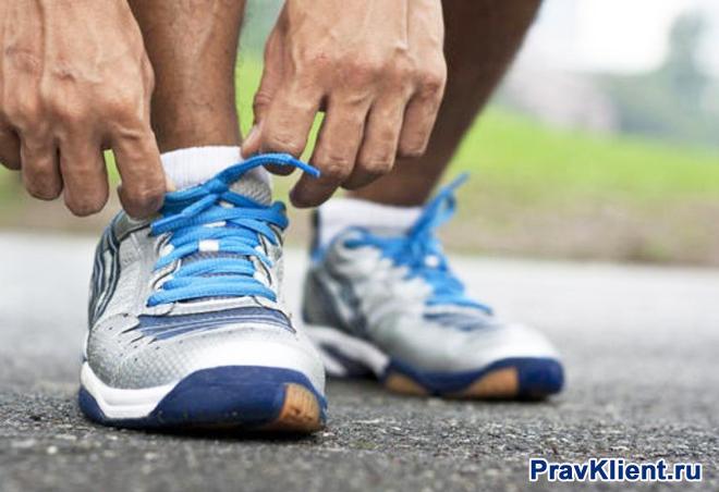 Спортсмен поправляет шнурки на кроссовке