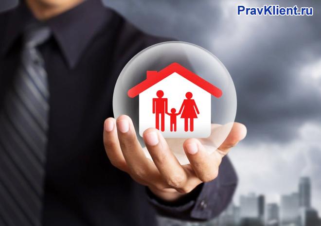Мужчина держит в руке домик, в котором живет семья