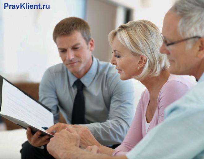 Мужчина консультирует по документации семейную пару