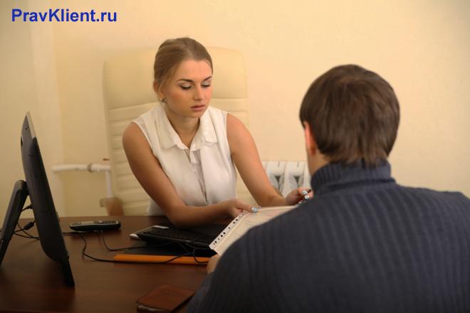 Сотрудница принимает в офисе клиента фирмы