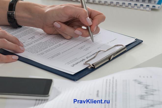 Женщина оформляет документы за столом
