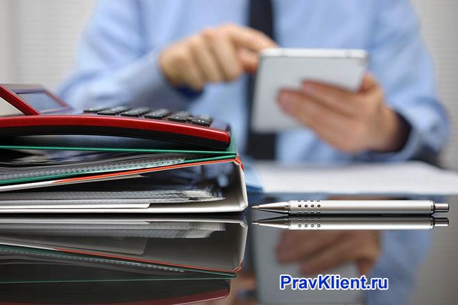 Бизнесмен считает на калькуляторе, рядом лежат папки с документами