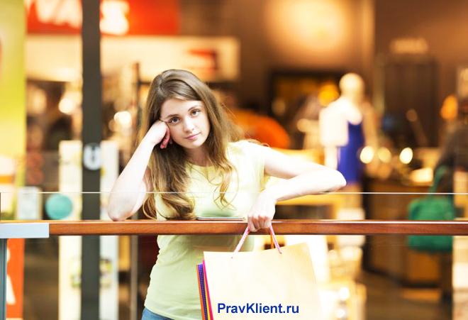 Девушка стоит с покупками в торговом центре