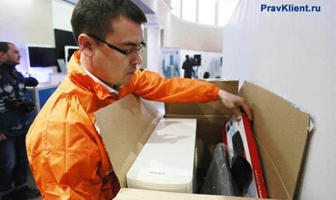 Мужчина распаковывает коробку с покупкой