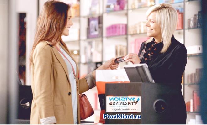 Девушка расплачивается за покупку банковской карточкой