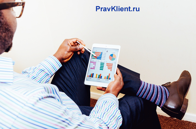 Бизнесмен смотрит в планшете графики