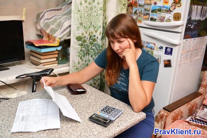 Девушка считает коммунальную плату на кухне