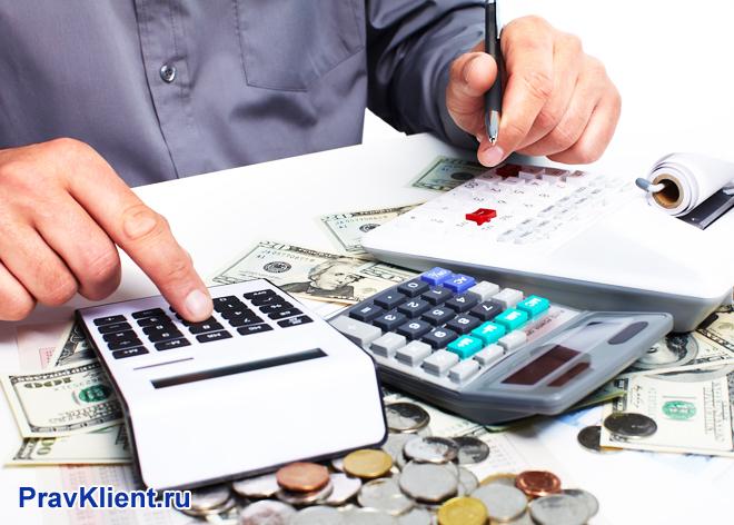 Мужчина пересчитывает деньги на калькуляторе