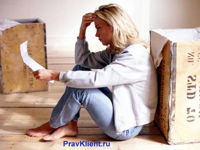 Девушка сидит на полу, читает бумагу рядом с картонными коробками