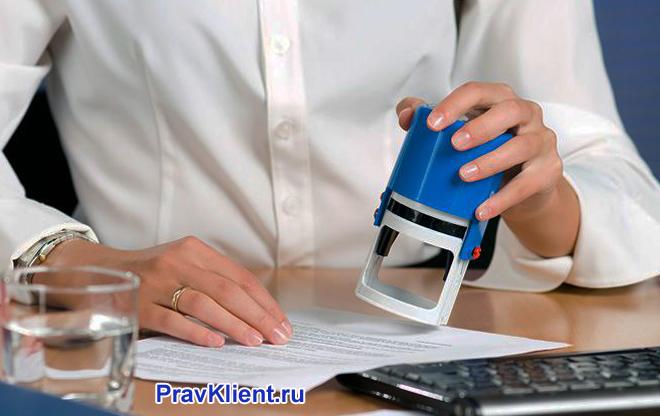 Девушка в белой рубашке ставит штамп на документе