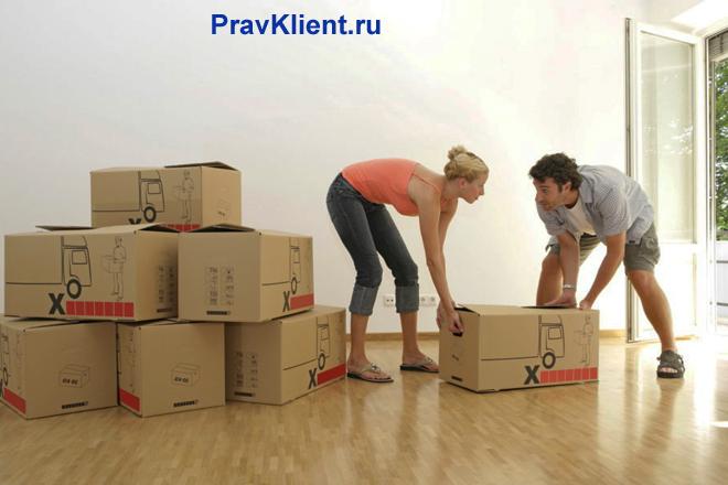Семейная пара вместе двигают коробки в комнате