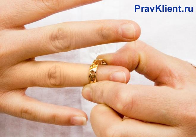 Мужчина снимает с пальца обручальное кольцо