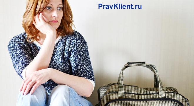 Задумчивая женщина сидит  около стены с сумкой