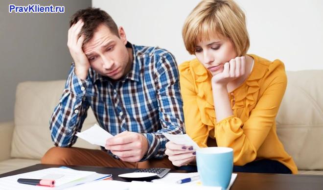 Мужчина и женщина сидят за столом, пьют чай, читают документы