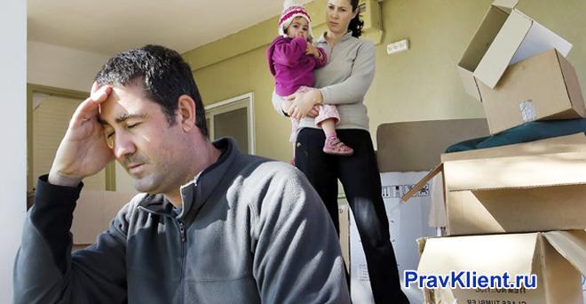 Женщина с ребенком на руках ругает мужчину, в комнате собраны вещи