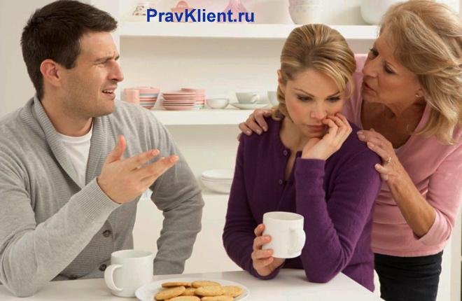 Семейная пара ругается на кухне, рядом стоит свекровь