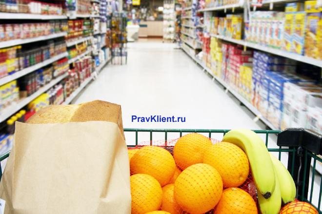 Покупатель идет с продуктовой корзиной по торговому залу