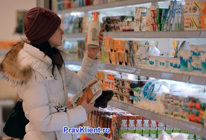 Девушка берет молоко с витрины